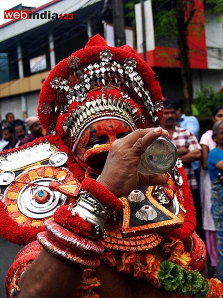 Theyyam, performer drinking water -Athachamayam 2013