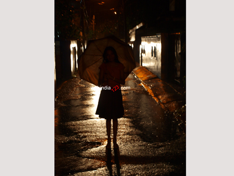 Girl standing in the rain holding an umbrella