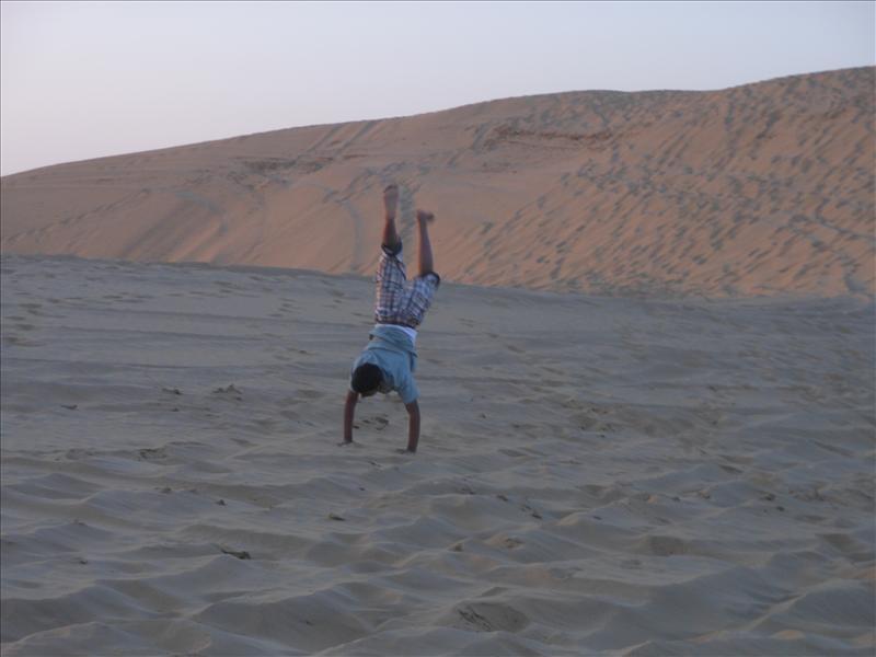a boy jumping on desert