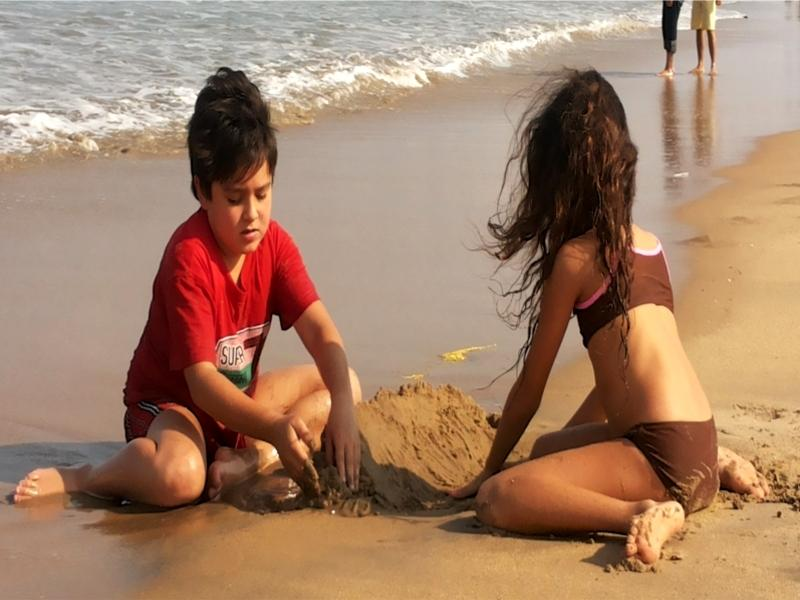 Innocent and cute kids playing on the shore.